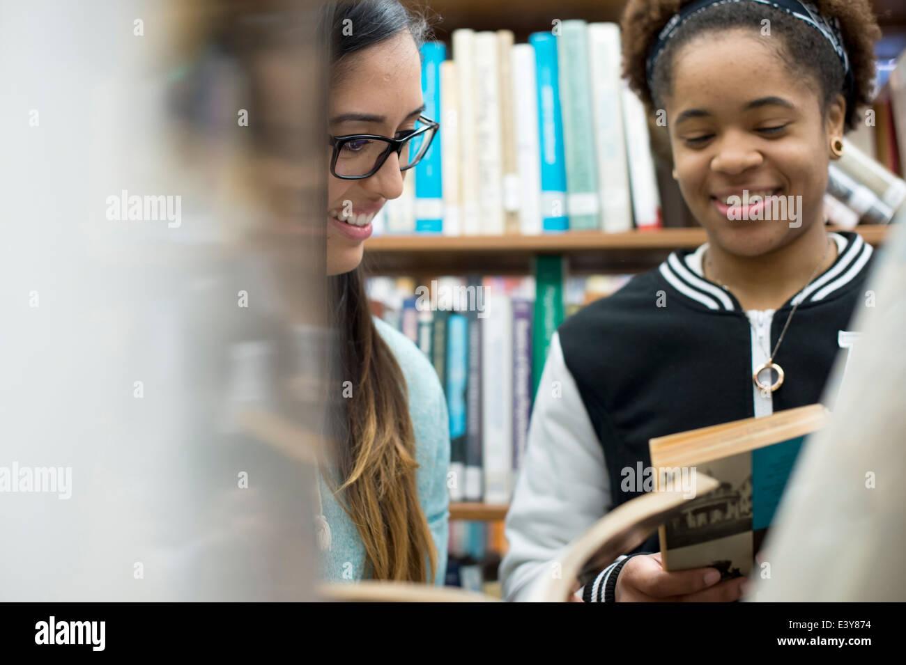 Los estudiantes universitarios eligiendo los libros en la biblioteca Imagen De Stock