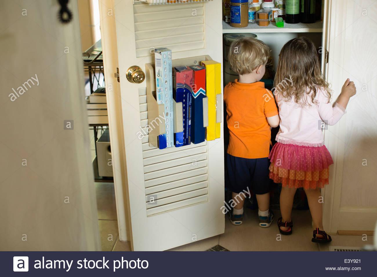 Macho y hembra toddler amigos buscando despensa Imagen De Stock