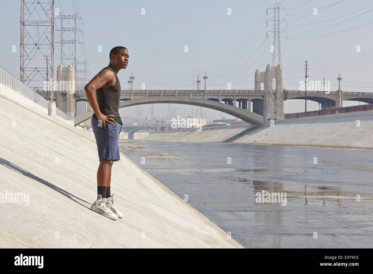 Macho joven corredor tomando un descanso en la ribera de la ciudad Imagen De Stock