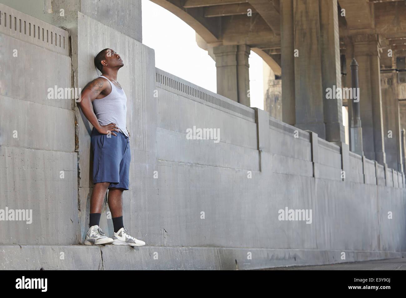 Agotado macho joven corredor inclinada contra el puente de la ciudad Imagen De Stock