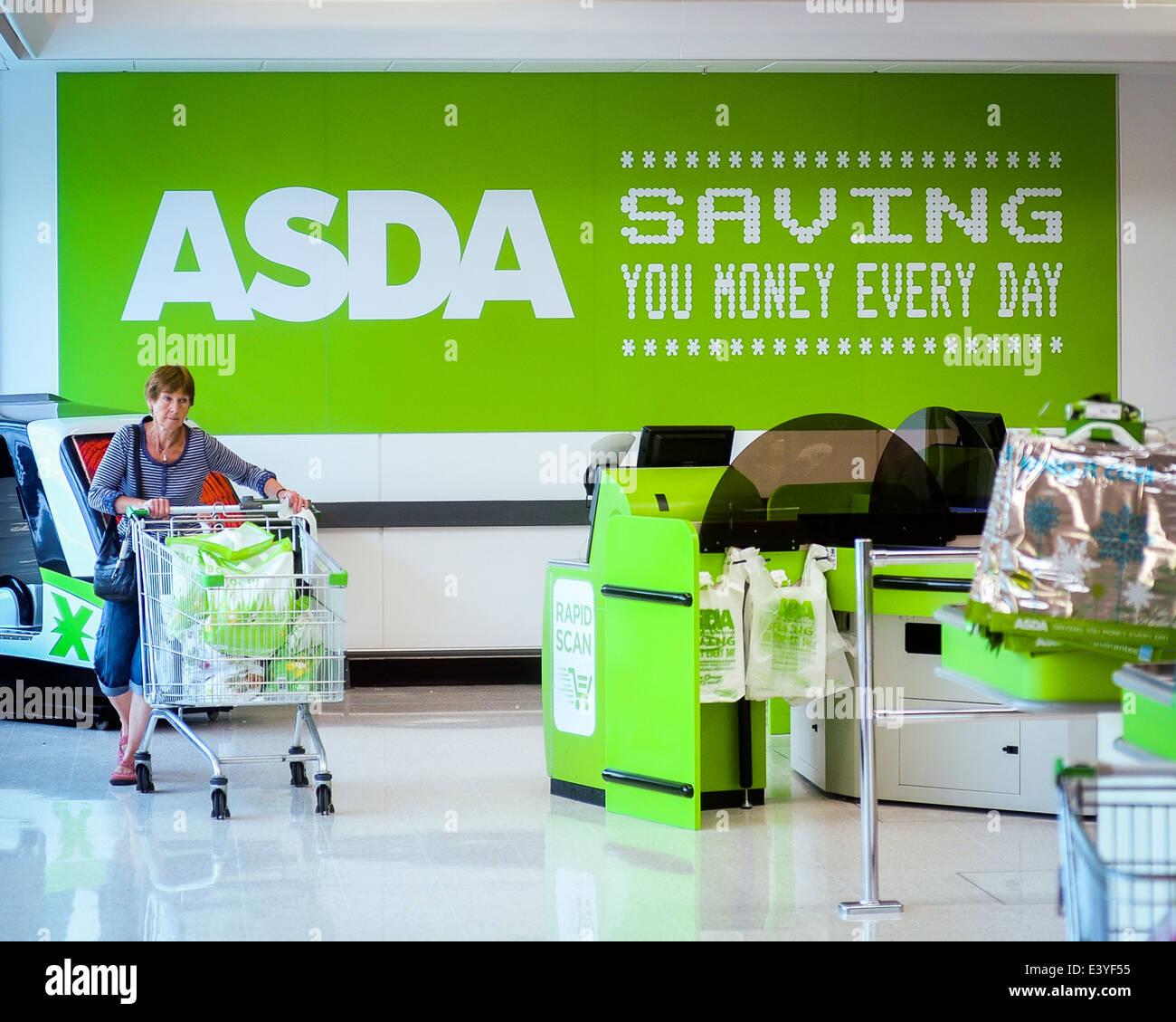 Mujer shopper con carro delante de ASDA logo - 'Saving dinero cada día' Imagen De Stock