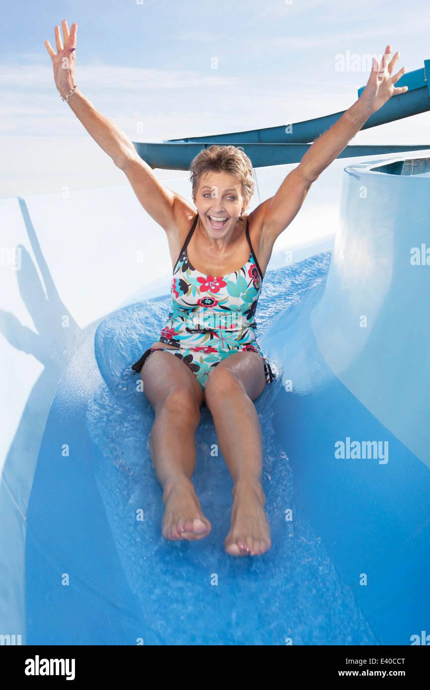 Feliz mujer senior deslizando hacia abajo el agua shute. Foto de stock