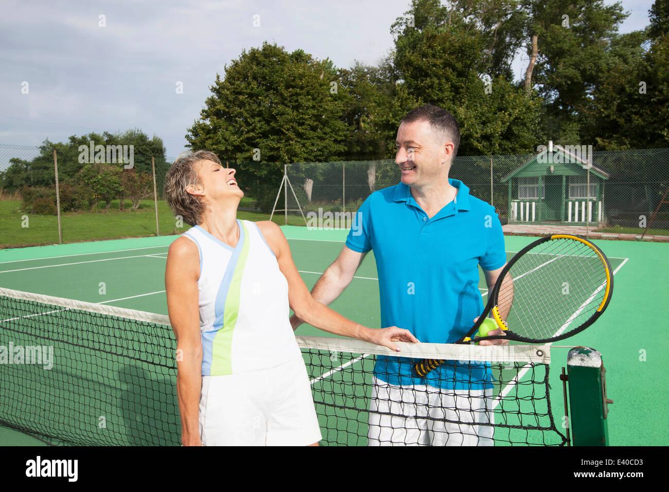 Las parejas ancianas conversando después de jugar tenis Foto de stock