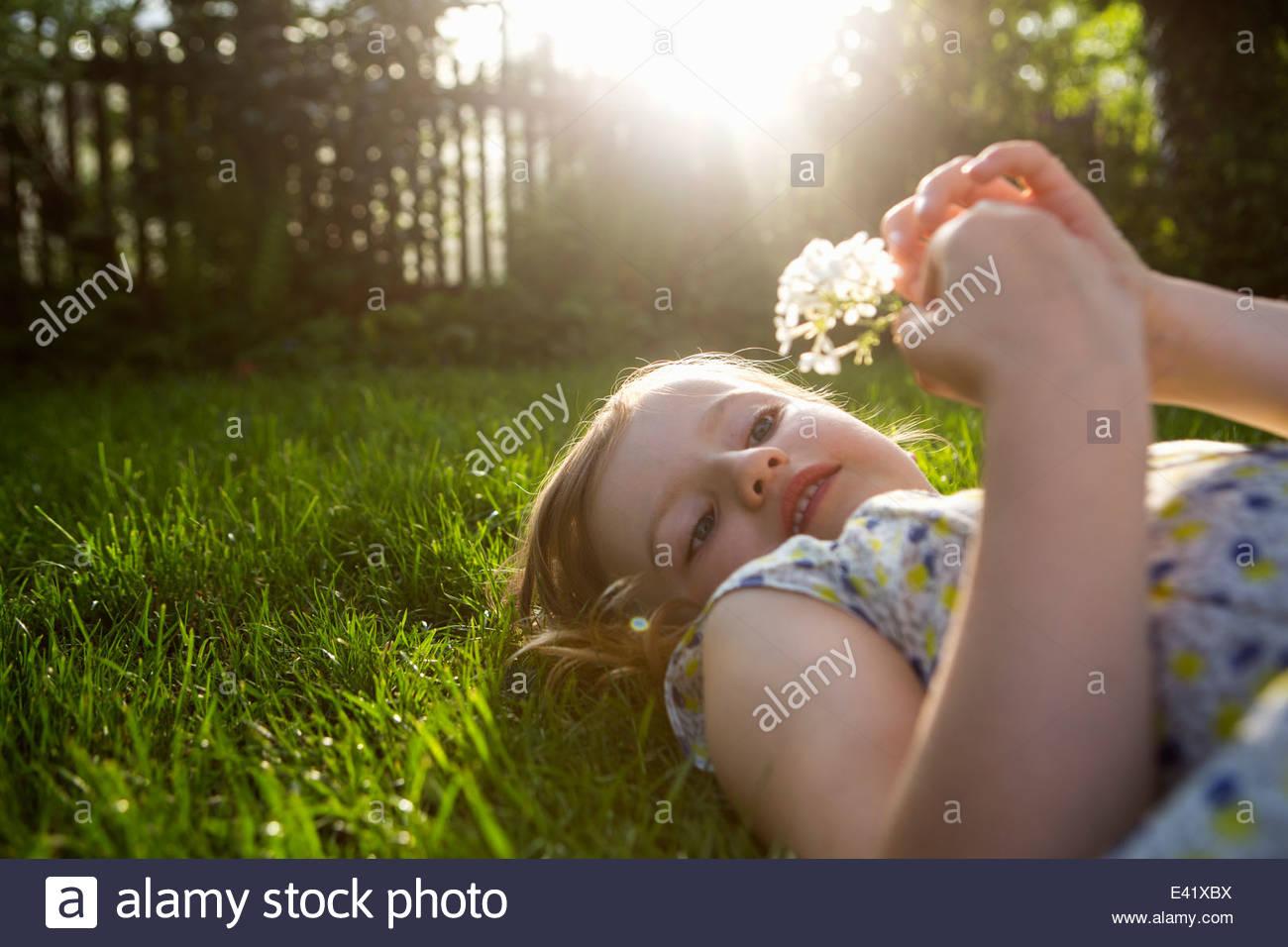 Chica con jaramago reloj, recostados sobre el pasto atrás Imagen De Stock