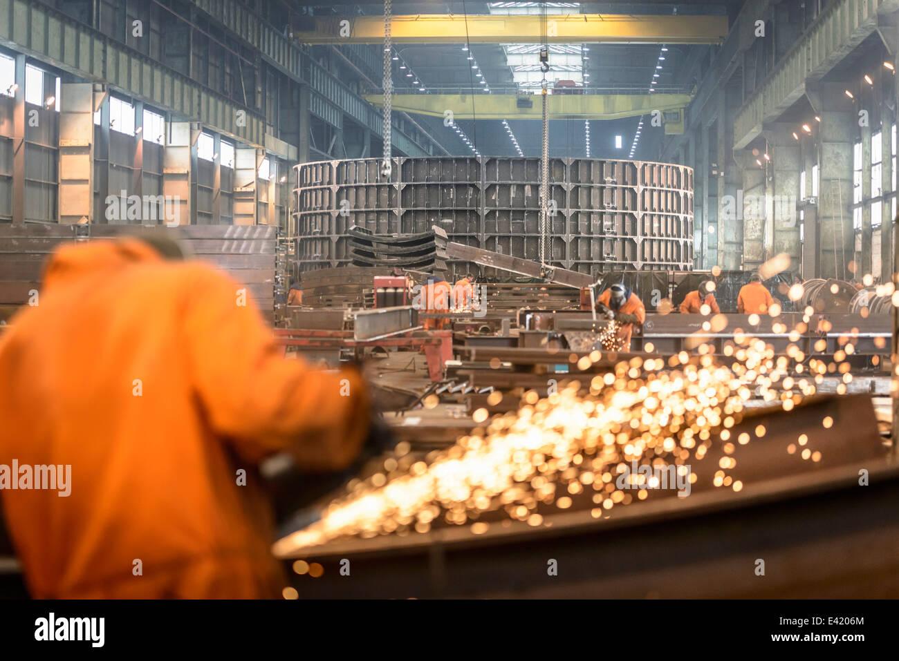 Trabajador de la construcción metálica de molienda en la fábrica de fabricación marina Imagen De Stock