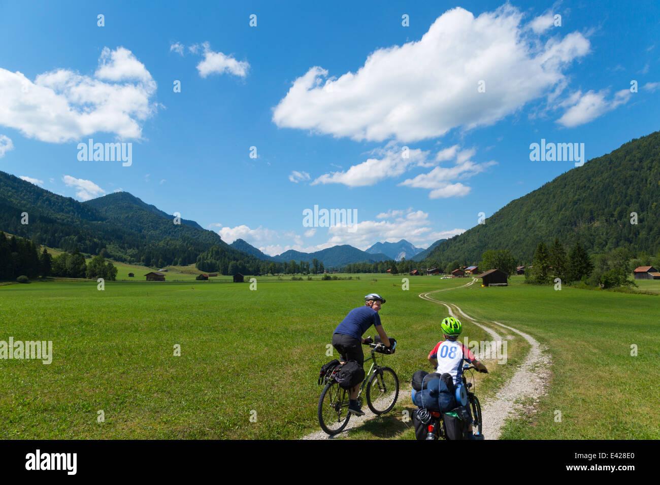 Padre e hijo en bicicleta a través de Jachenau, Baviera, Alemania Imagen De Stock