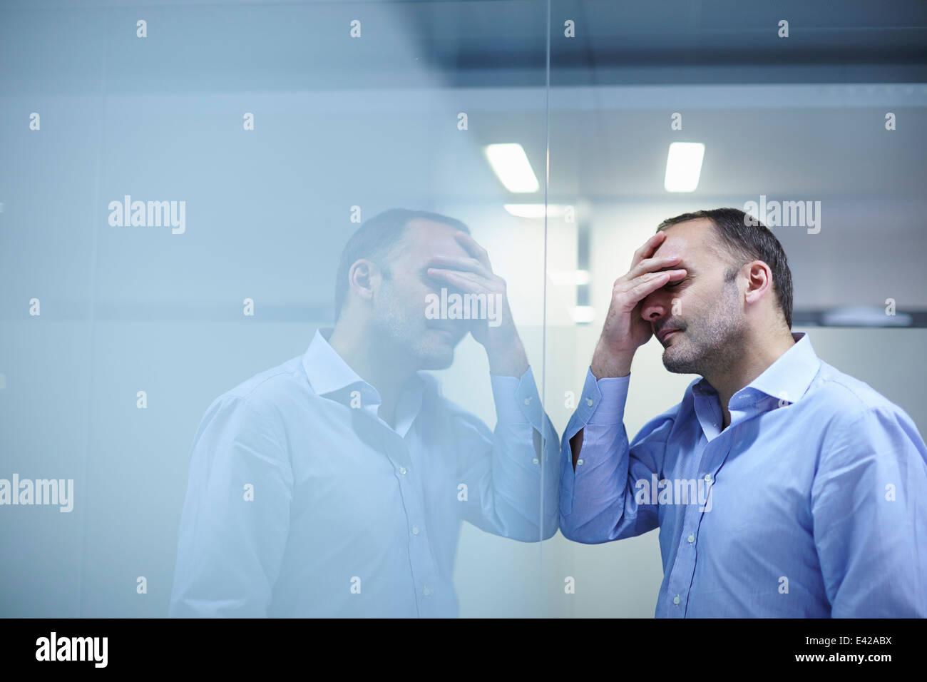 Hombre desesperado mirando la pared reflectante Foto de stock