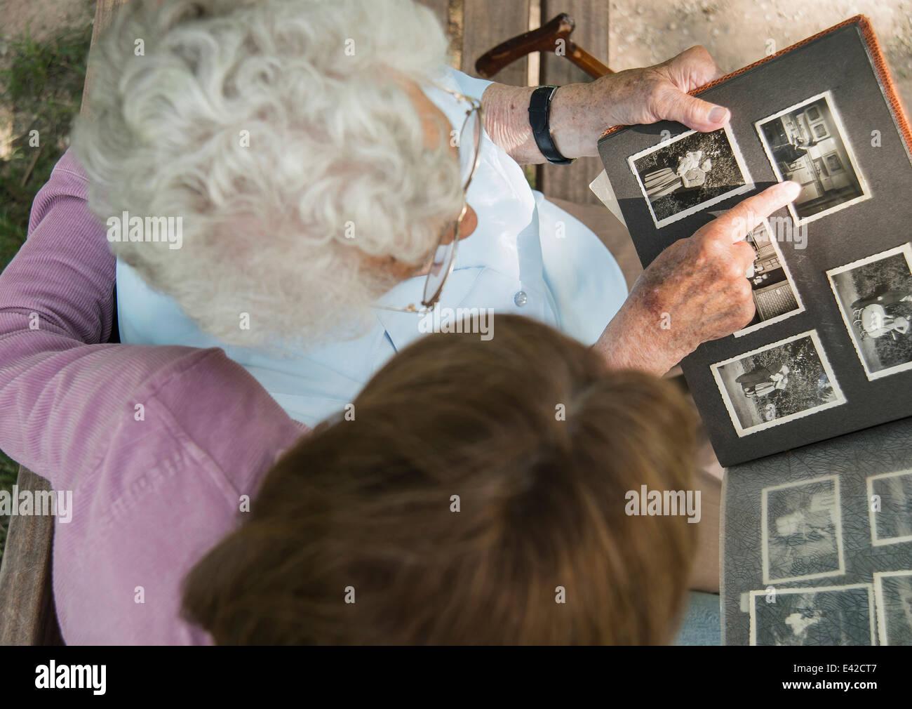 Senior mujer sentada en un banco del parque con su nieta, busca en el viejo álbum de fotografías Imagen De Stock