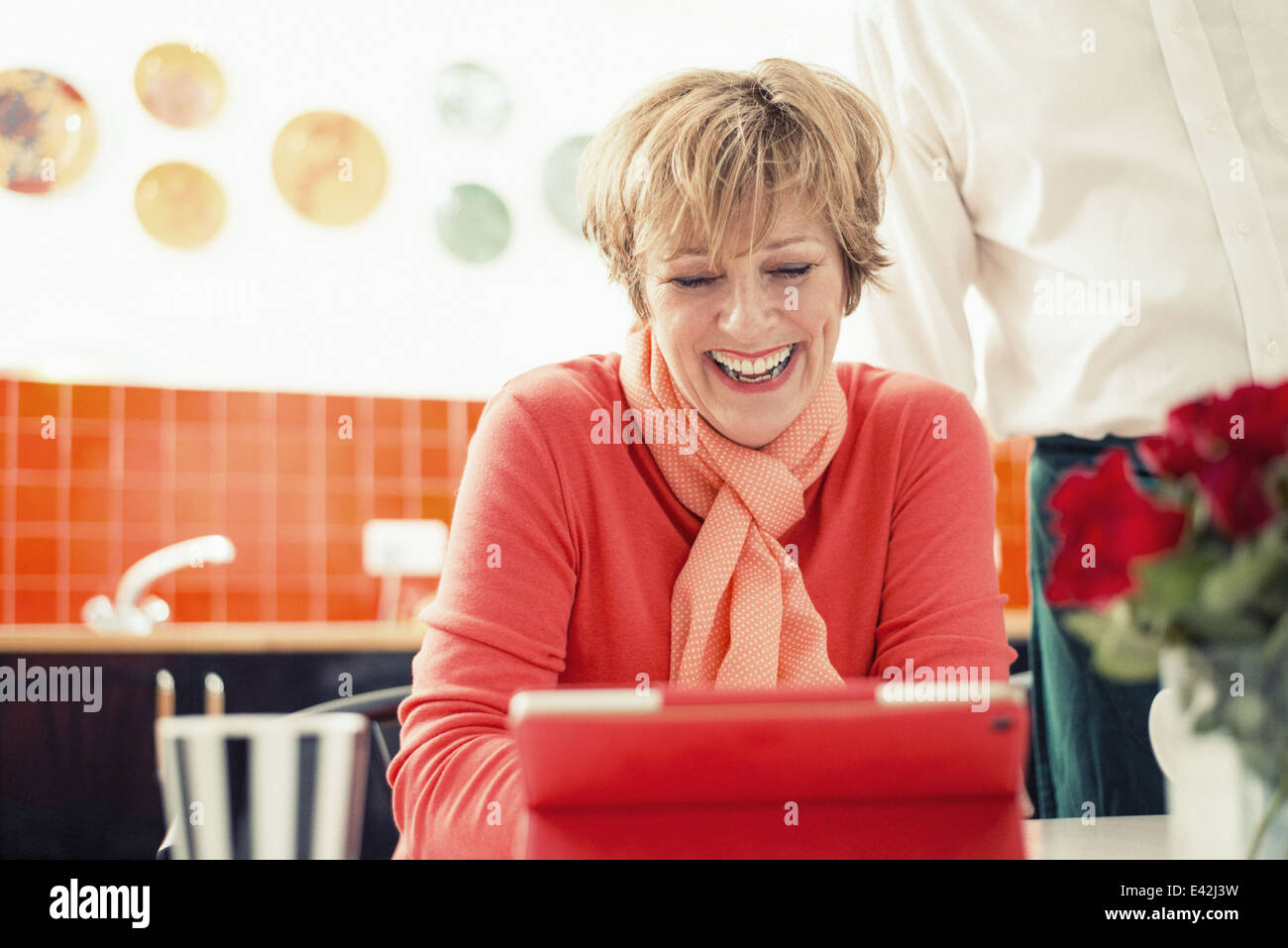Mujer madura con tableta digital en la cocina Foto de stock