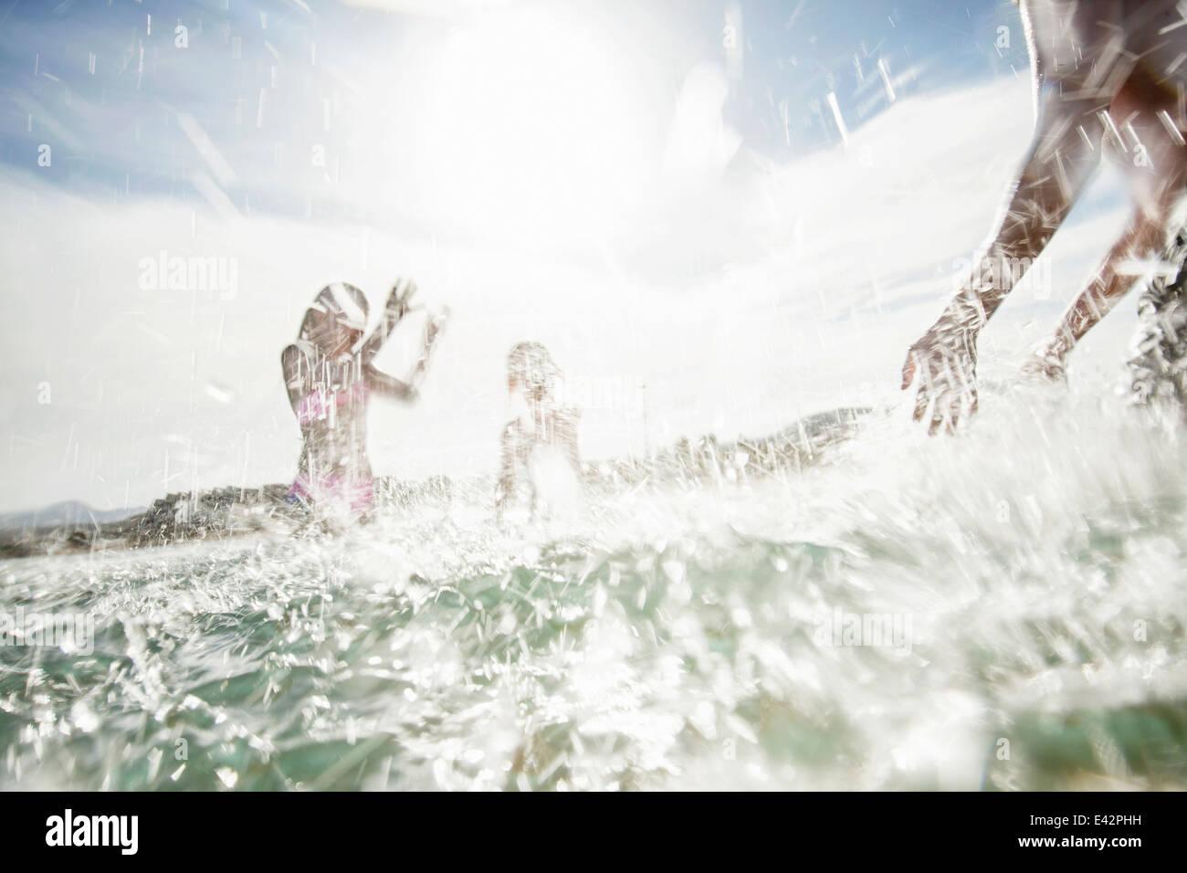 El padre con el hijo e hija salpicaduras mutuamente en la playa Imagen De Stock