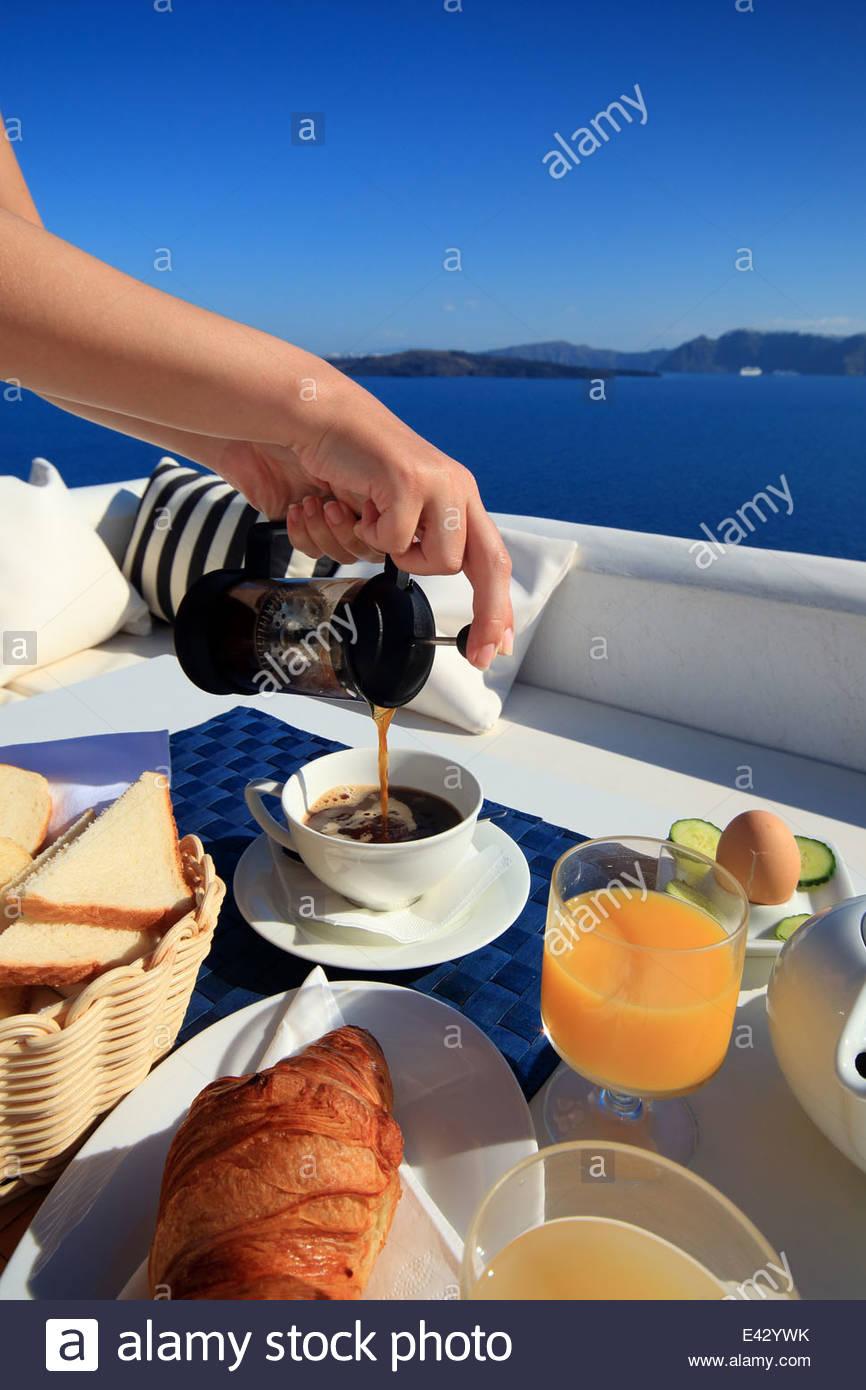 Manos femeninas, verter el café del desayuno en el balcón, Santorini, las Islas Cícladas, Grecia Imagen De Stock
