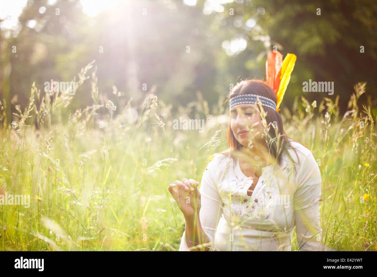 Mujer madura en Native American tocado en pasto largo Foto de stock