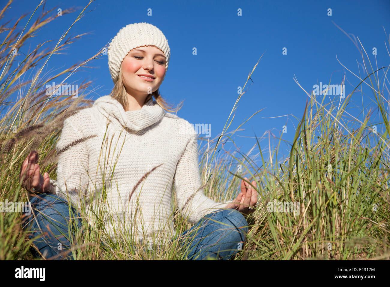 Mujer joven en posición de loto del yoga en el césped largo Imagen De Stock