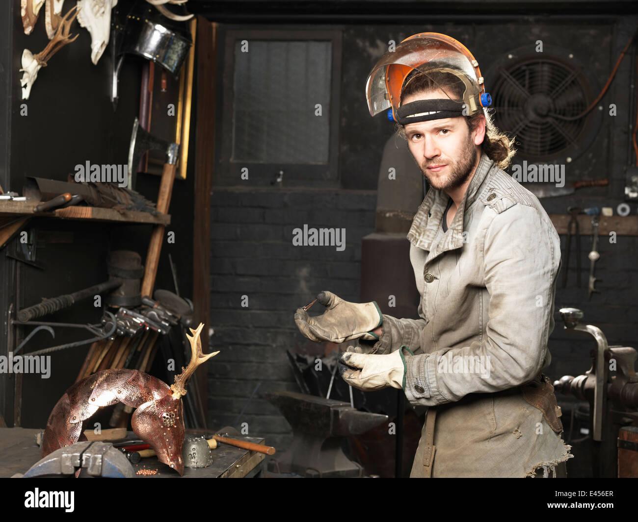 Retrato de herrero con un clavo de cobre en el taller Imagen De Stock