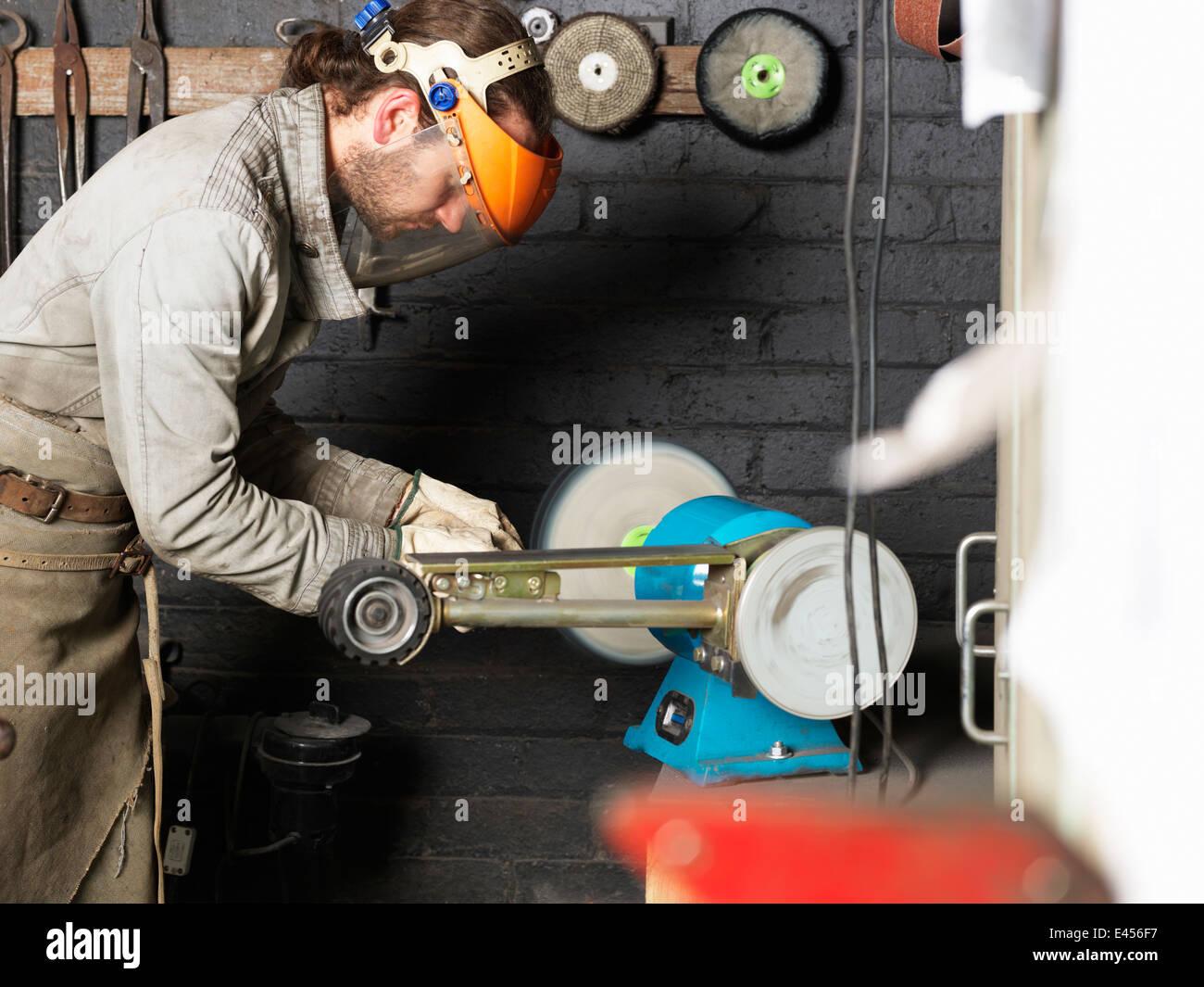 Herrero trabajando en la máquina en el taller Foto de stock