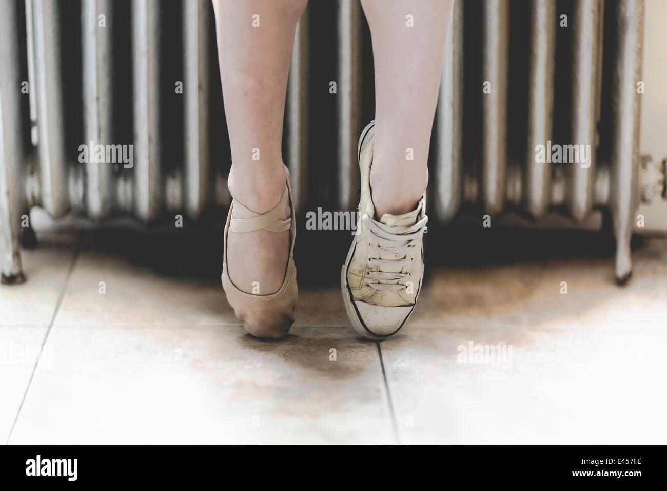 Bailarina de ballet lleva un zapato y una zapatilla. Imagen De Stock