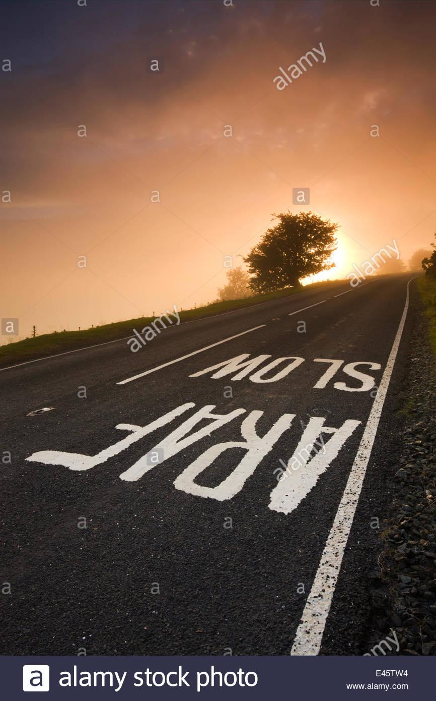 'Lento' pintados cartel en una carretera en un páramo brumoso del amanecer, el Parque Nacional de Brecon Imagen De Stock