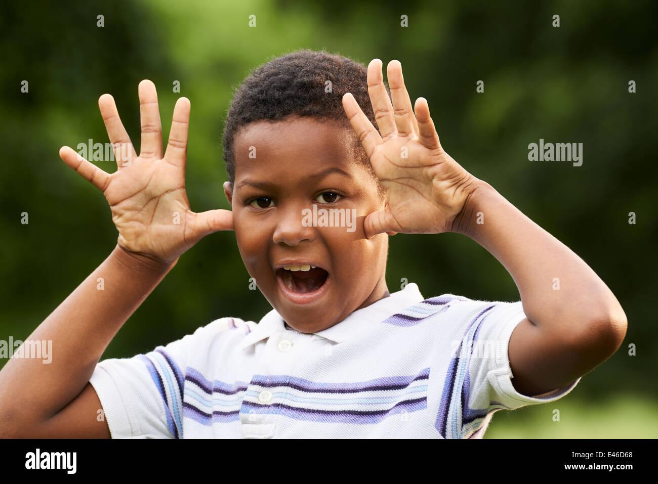 Retrato de niño negro feliz haciendo una cara y hacer muecas en la cámara al aire libre en el parque Imagen De Stock