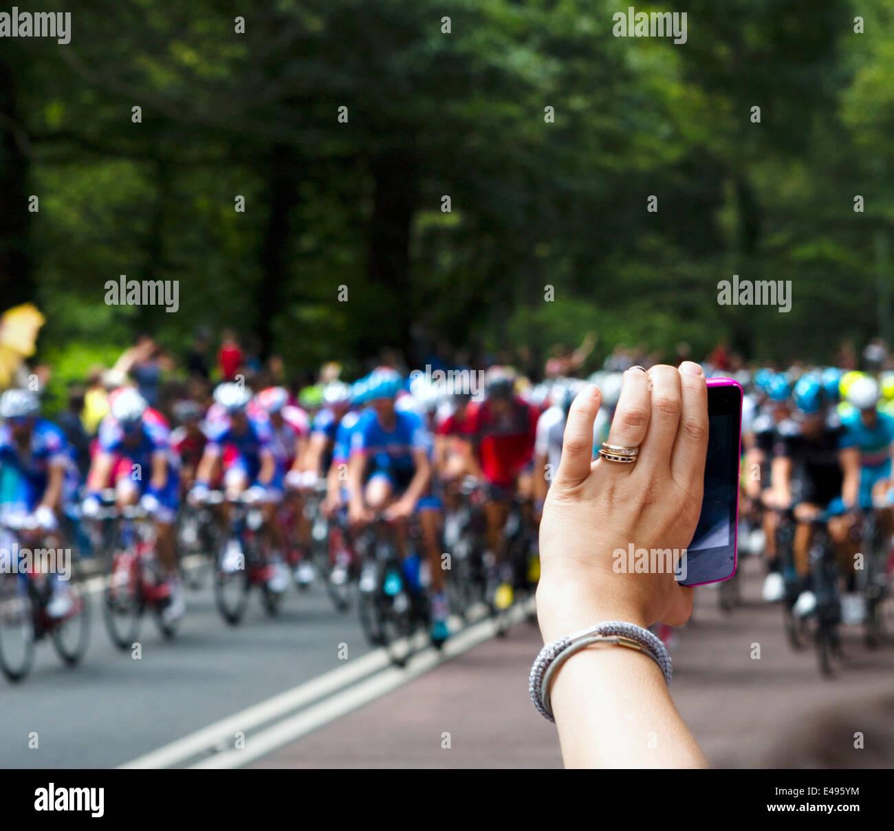 Mujer toma una foto con un smartphone de la Holmfirth peleton acercándose en la etapa 2 del Tour de Francia Imagen De Stock