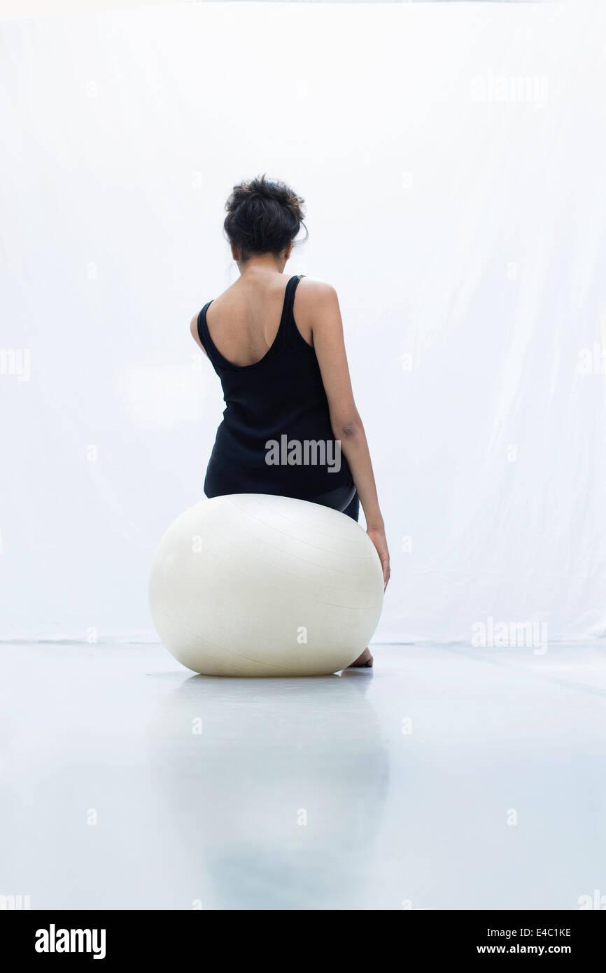 Equilibrio de la mujer sobre la bola del yoga vista trasera foto de estudio Foto de stock