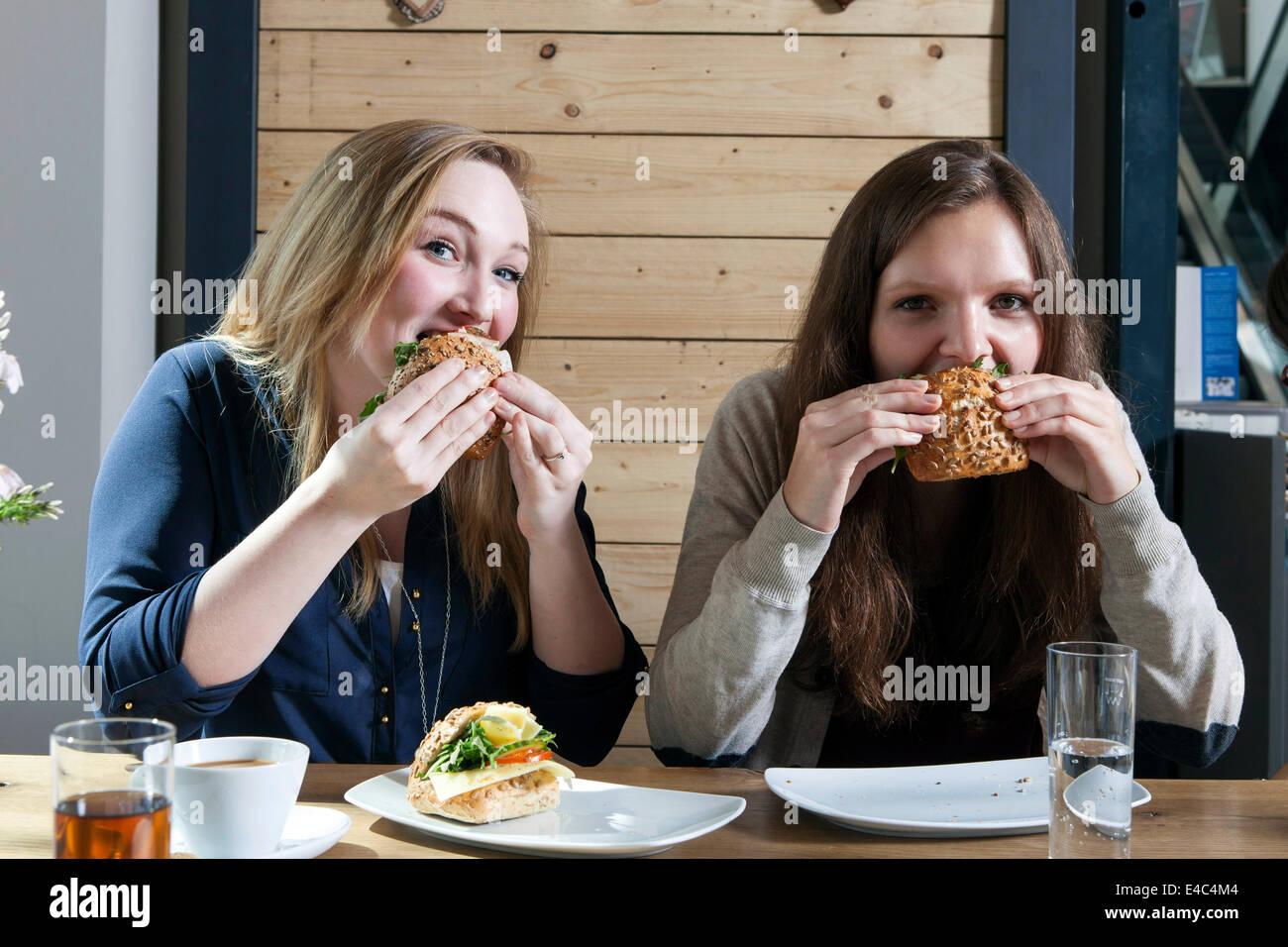 Dos jóvenes mujeres comer bocadillos en la cafetería Imagen De Stock