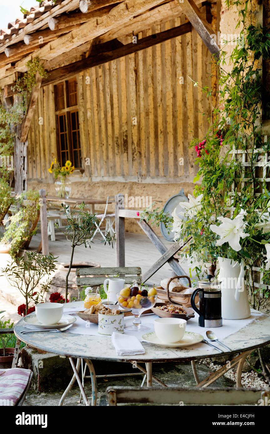 El desayuno sentado en la mesa redonda con plegado bistro sillas en patio de antiguo establo Imagen De Stock