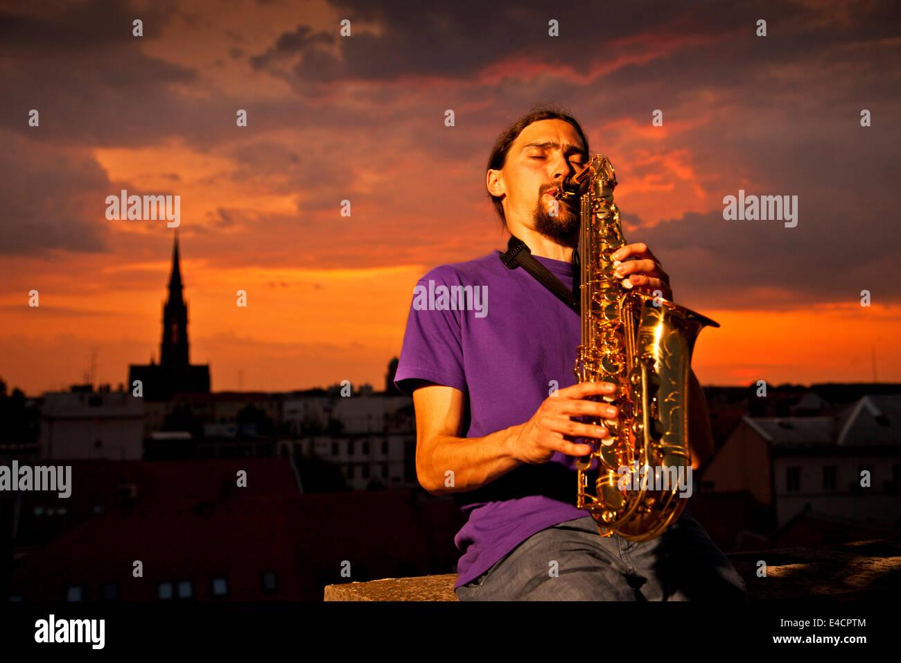 Hombre tocando el saxofón en el sunset, en Osijek, Croacia Imagen De Stock