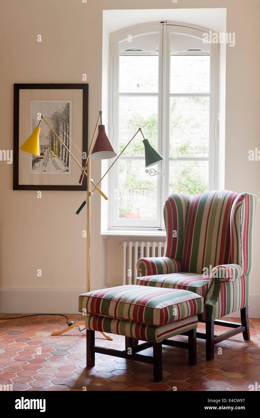 Wingback rayas sillón con heces coincidente en la habitación con baldosas de terracota honeycomb Imagen De Stock
