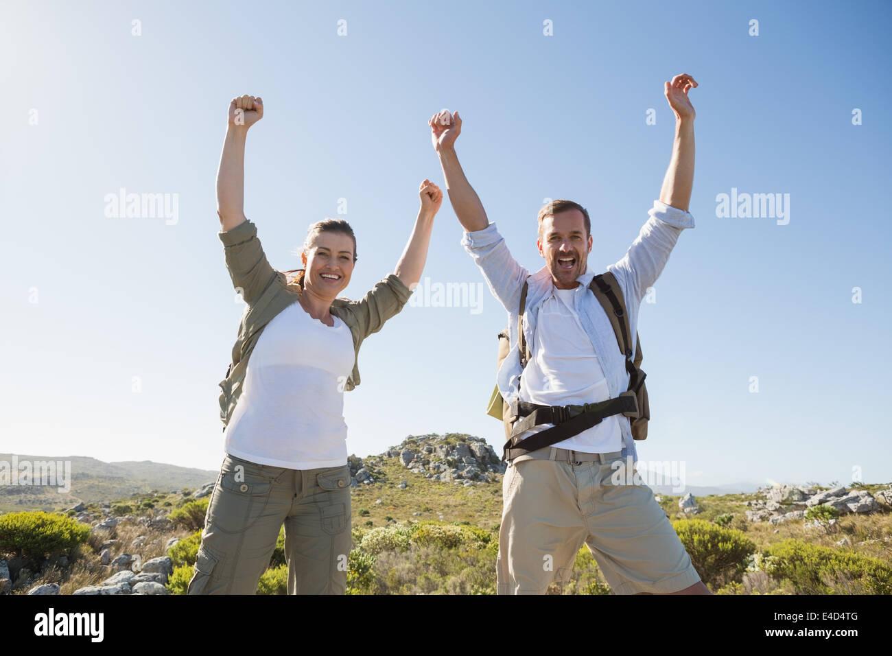Senderismo par vitoreando en cámara en terreno montañoso Imagen De Stock