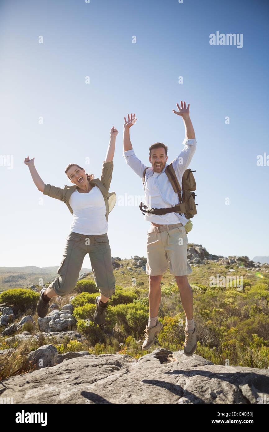 Senderismo par saltando y vitoreando sobre terreno rocoso Imagen De Stock