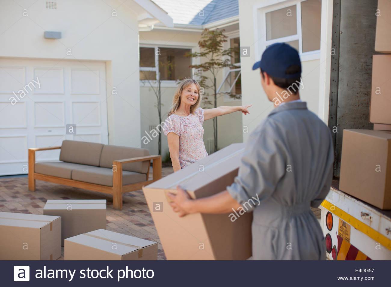 El transportador ayudando mujer mudarse a Nueva Casa Imagen De Stock