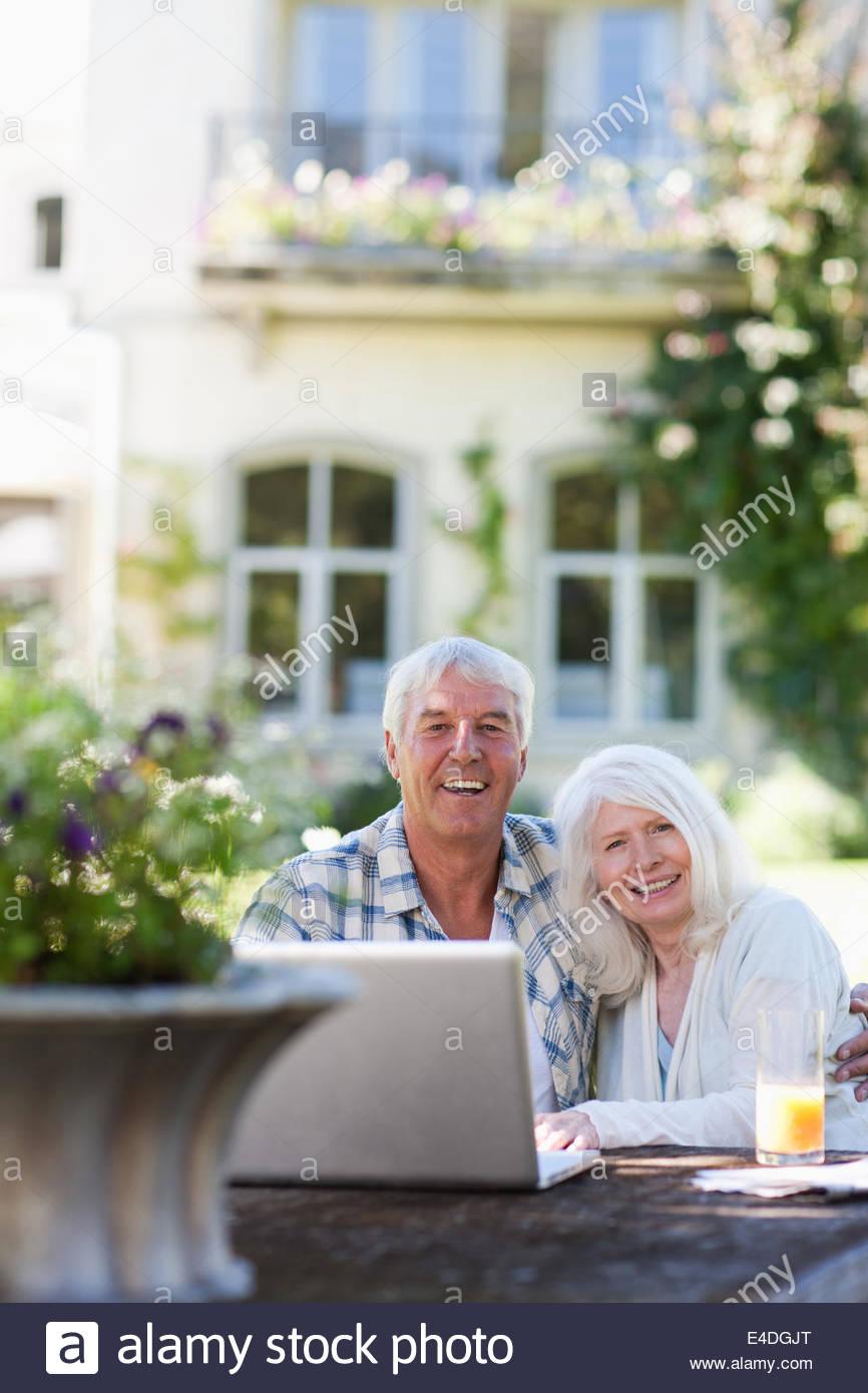 Senior pareja utilizando el portátil en una mesa en el jardín Imagen De Stock