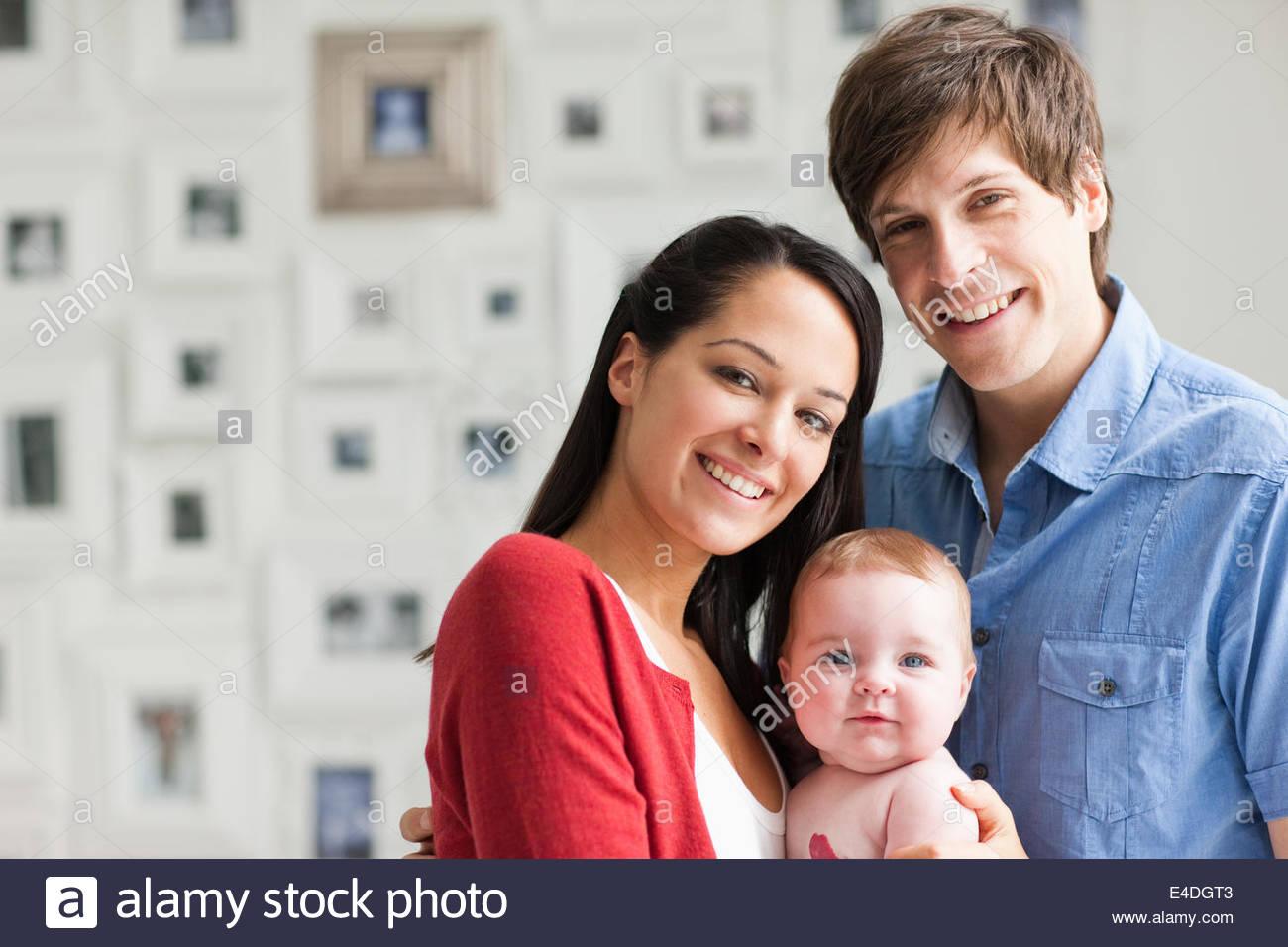 Los padres sonriente Celebración de bebé Imagen De Stock