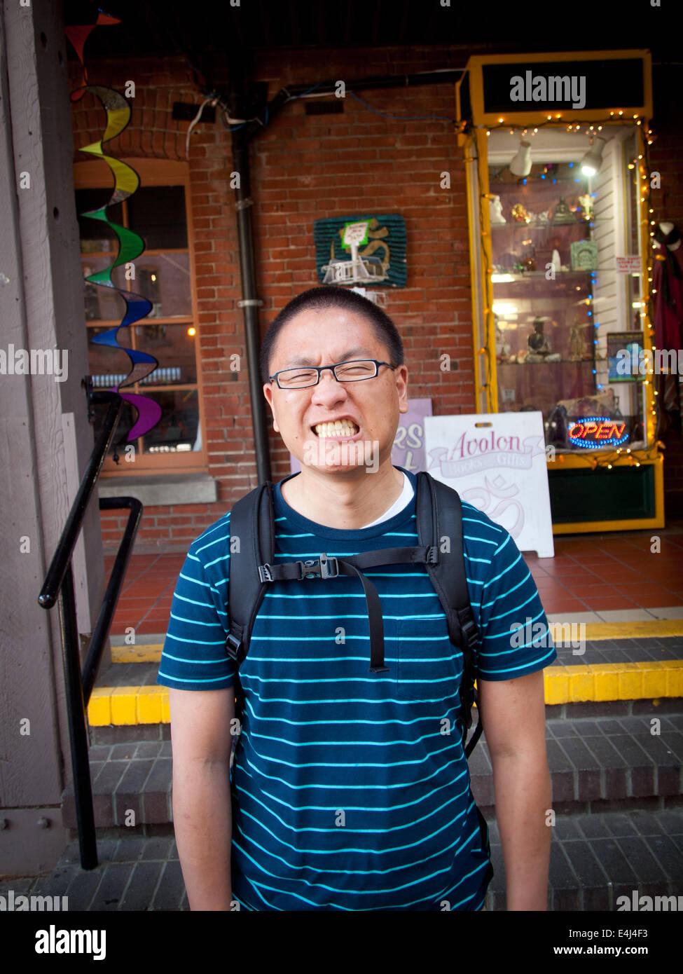 Un hombre asiático muecas. La plaza del mercado, Victoria, British Columbia, Canadá. *** Modelo de liberación Imagen De Stock