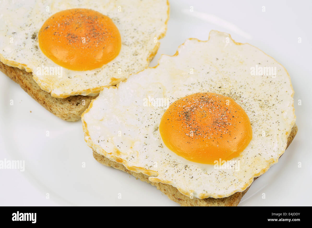 Dos huevos fritos con sal y pimienta sobre una tostada, cerca de la placa blanca, full frame Imagen De Stock