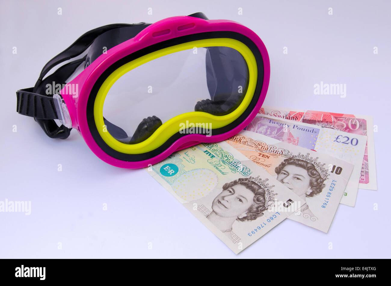 Máscara de Snorkel con British Pound notas sobre fondo blanco. Foto de stock