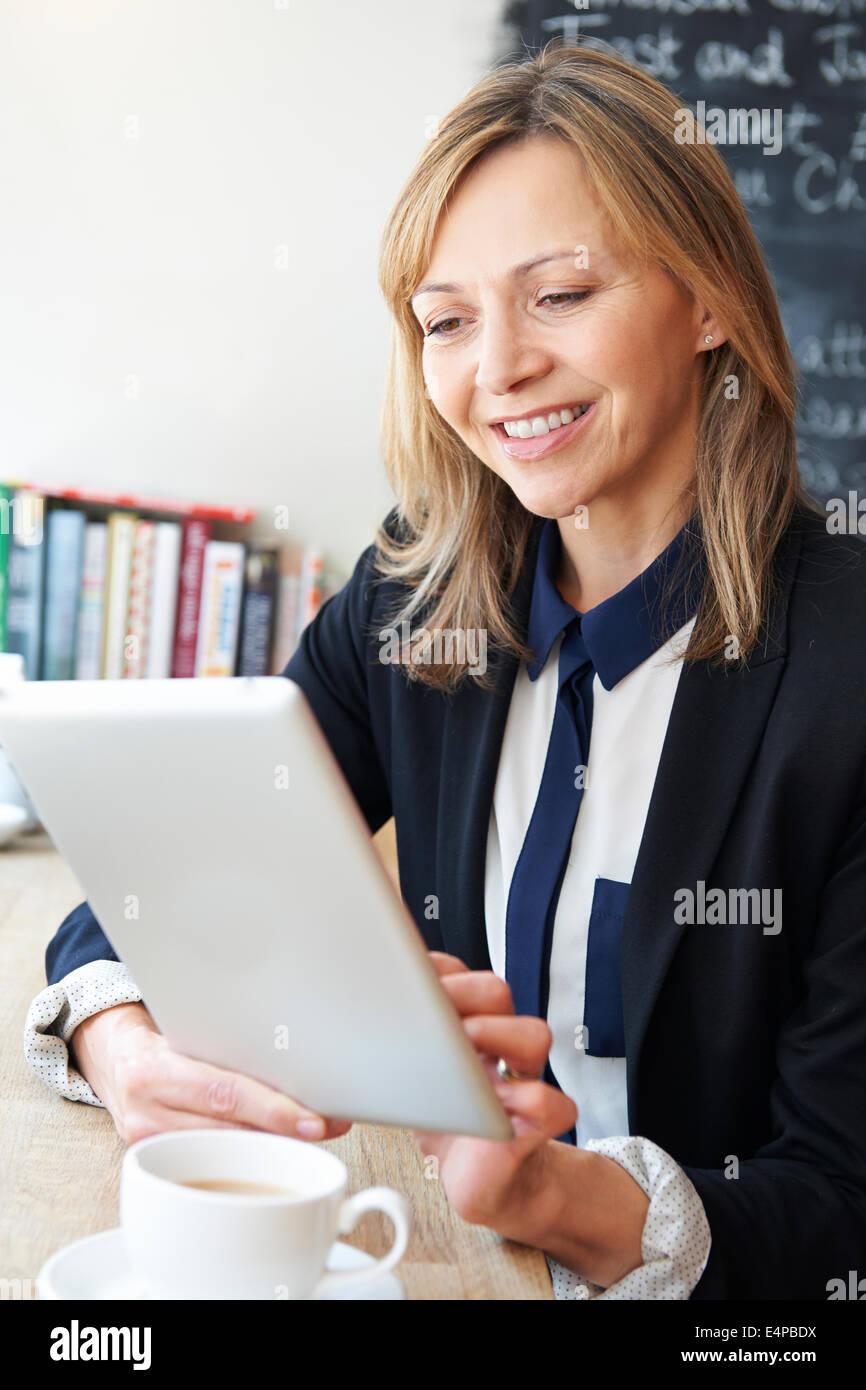 La empresaria mediante Digital comprimido en Cafe Imagen De Stock