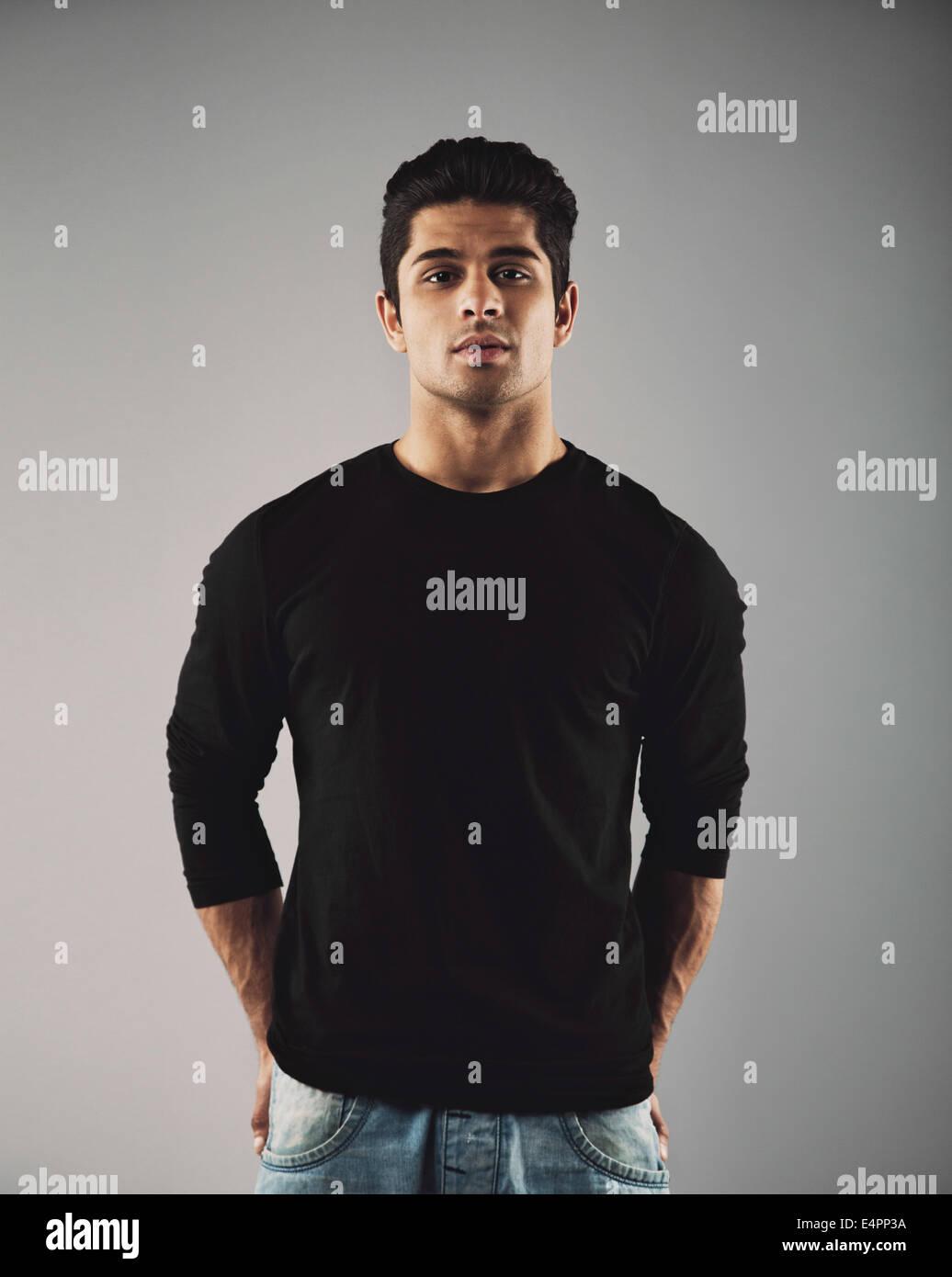 Retrato de joven apuesto chico hispano posando. Smart modelo moda masculina posando sobre fondo gris. Imagen De Stock