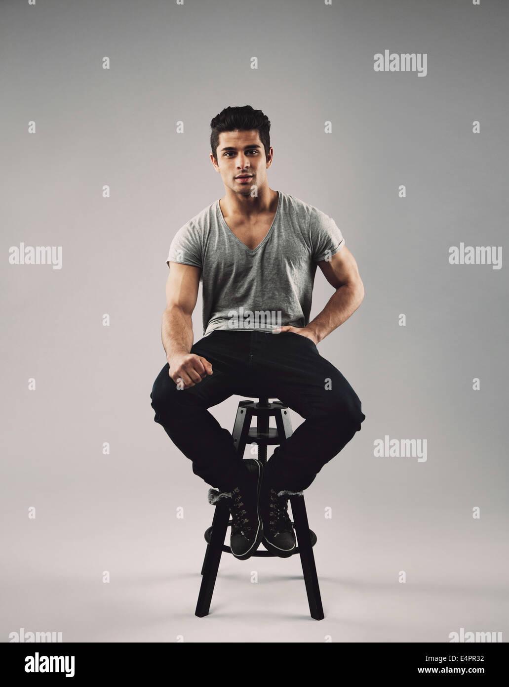 Retrato de smart joven sentado en las heces. Atractivo modelo masculino posando sobre fondo gris. Imagen De Stock