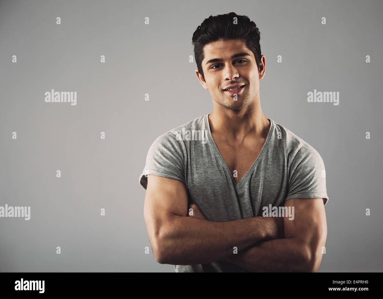 Retrato de un joven apuesto de pie con los brazos cruzados sobre fondo gris con espacio de copia. Moda masculina Imagen De Stock