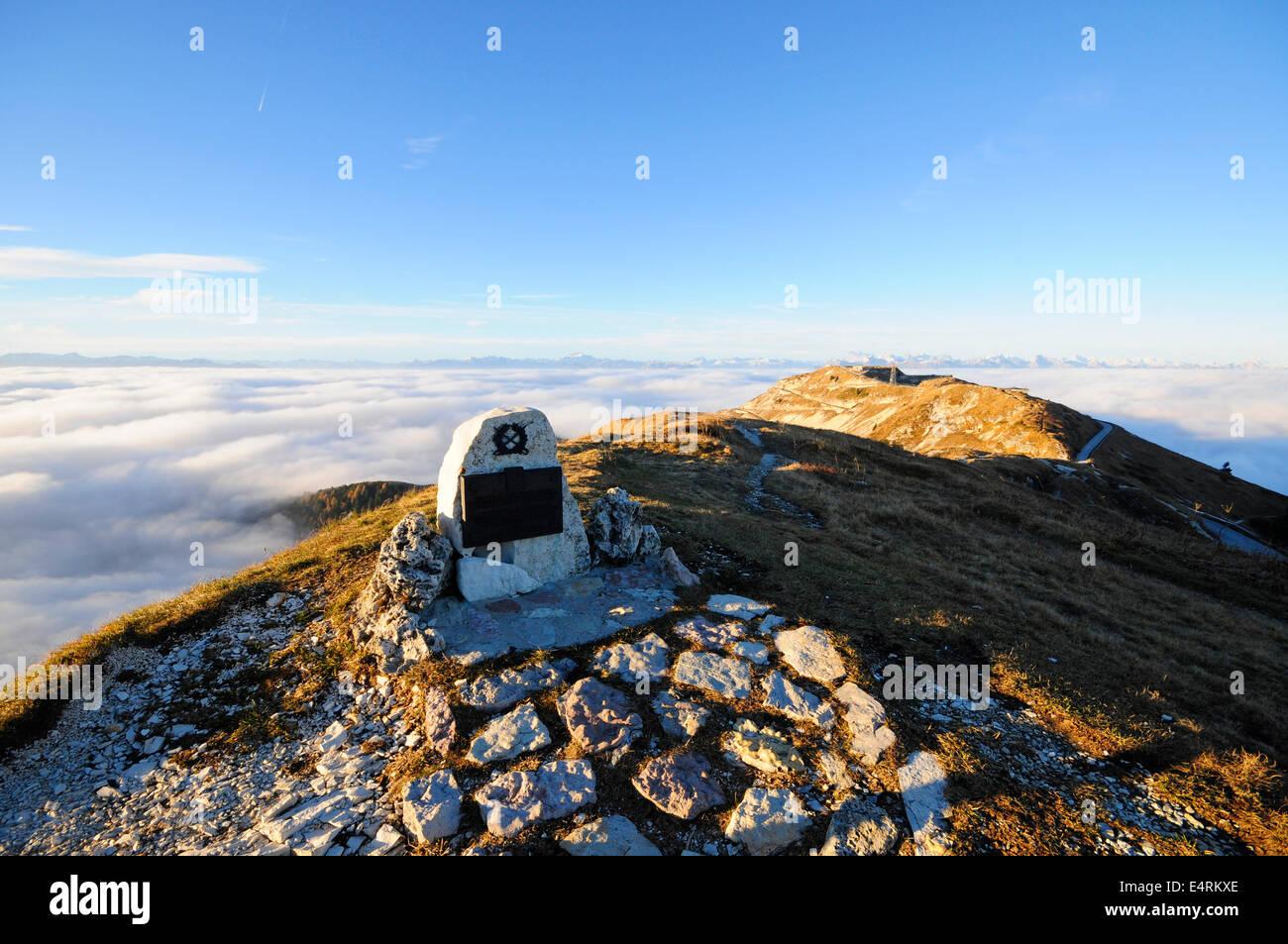 Monumento militar en la cima de una montaña con una luz que emerge de las nubes Foto de stock