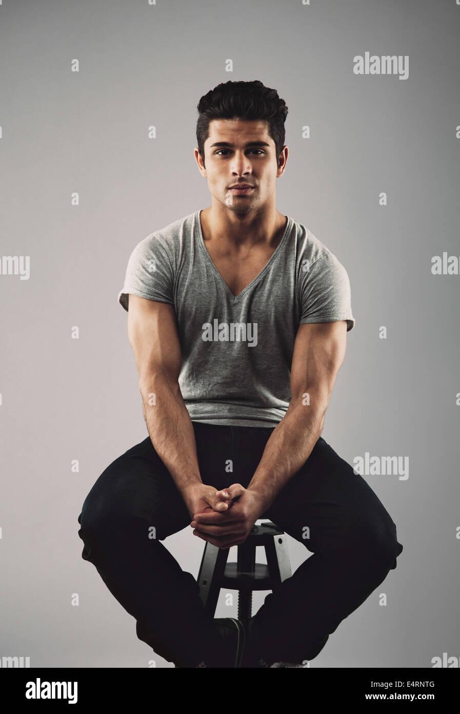 Retrato del joven muscular modelo masculino sentado en heces. Joven hispana sobre fondo gris. Imagen De Stock