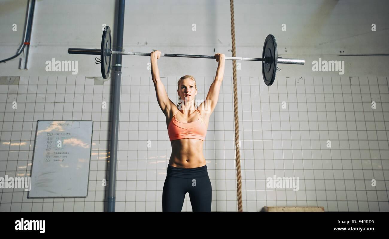 La atleta femenina joven muscular haciendo pesas en el gimnasio crossfit. Colocar joven modelo levantar pesos pesados Imagen De Stock