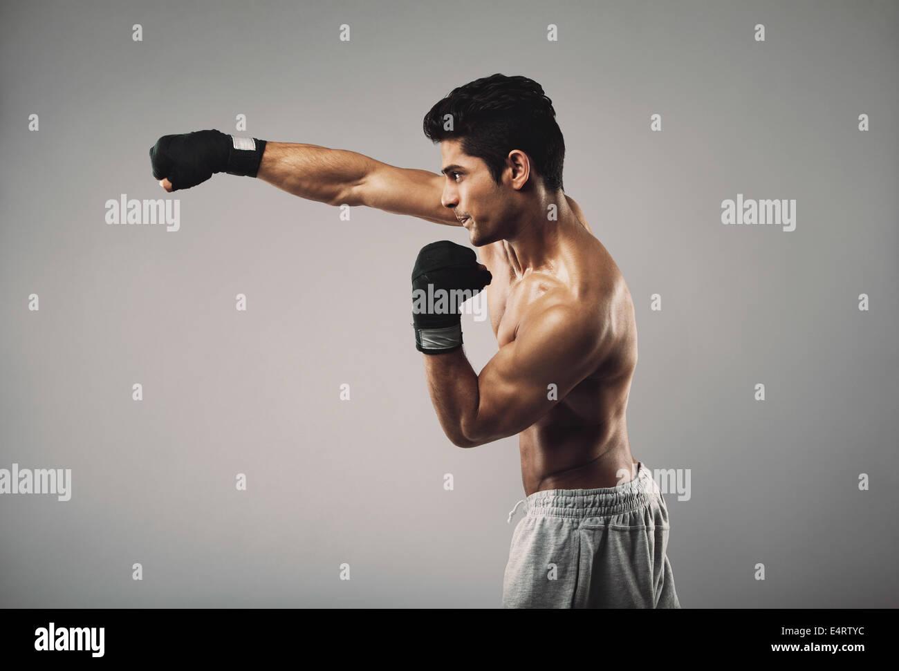 Ver perfil de joven practicando shadowboxing sobre fondo gris. Joven modelo masculino de trabajo muscular. Imagen De Stock