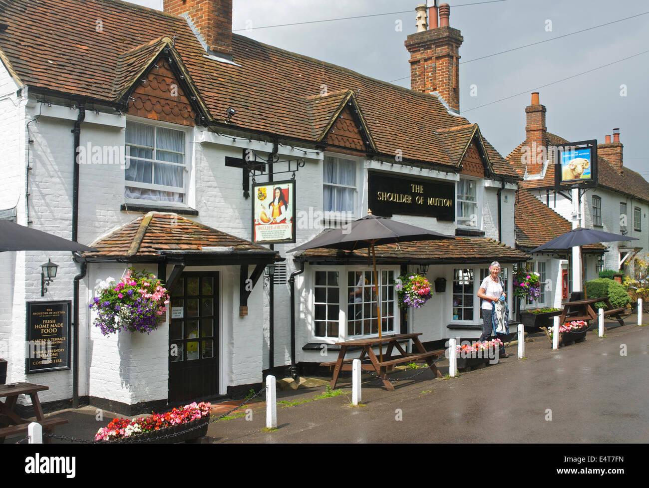 Mujer mayor dejando la paletilla de cordero en Hazeley Heath, un pub cerca de Hartley Wintney, Hampshire, Inglaterra Imagen De Stock