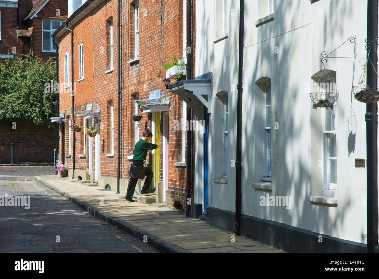 El colegial entrando en casa en Farnham, Surrey, Inglaterra Imagen De Stock