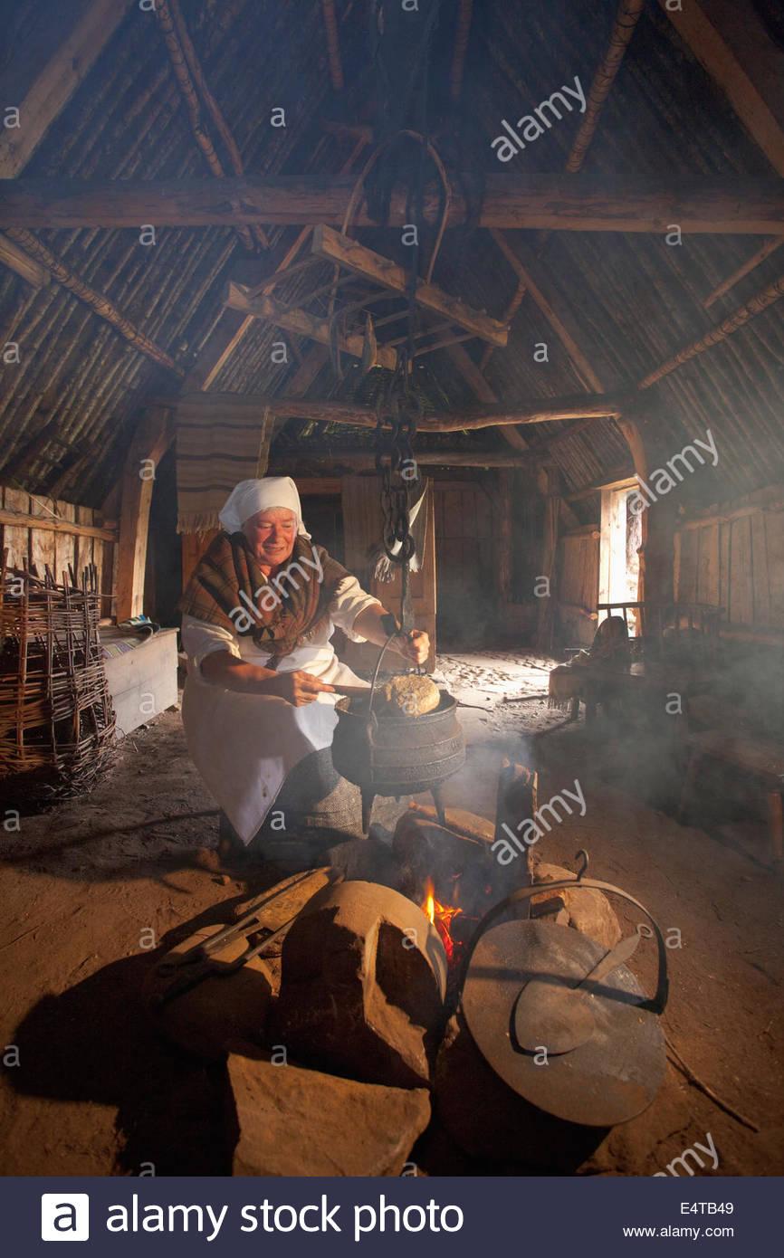 Una mujer en traje tradicional cocina en la manera tradicional en la Highland Folk Museum, Newtonmore, Highlands Imagen De Stock