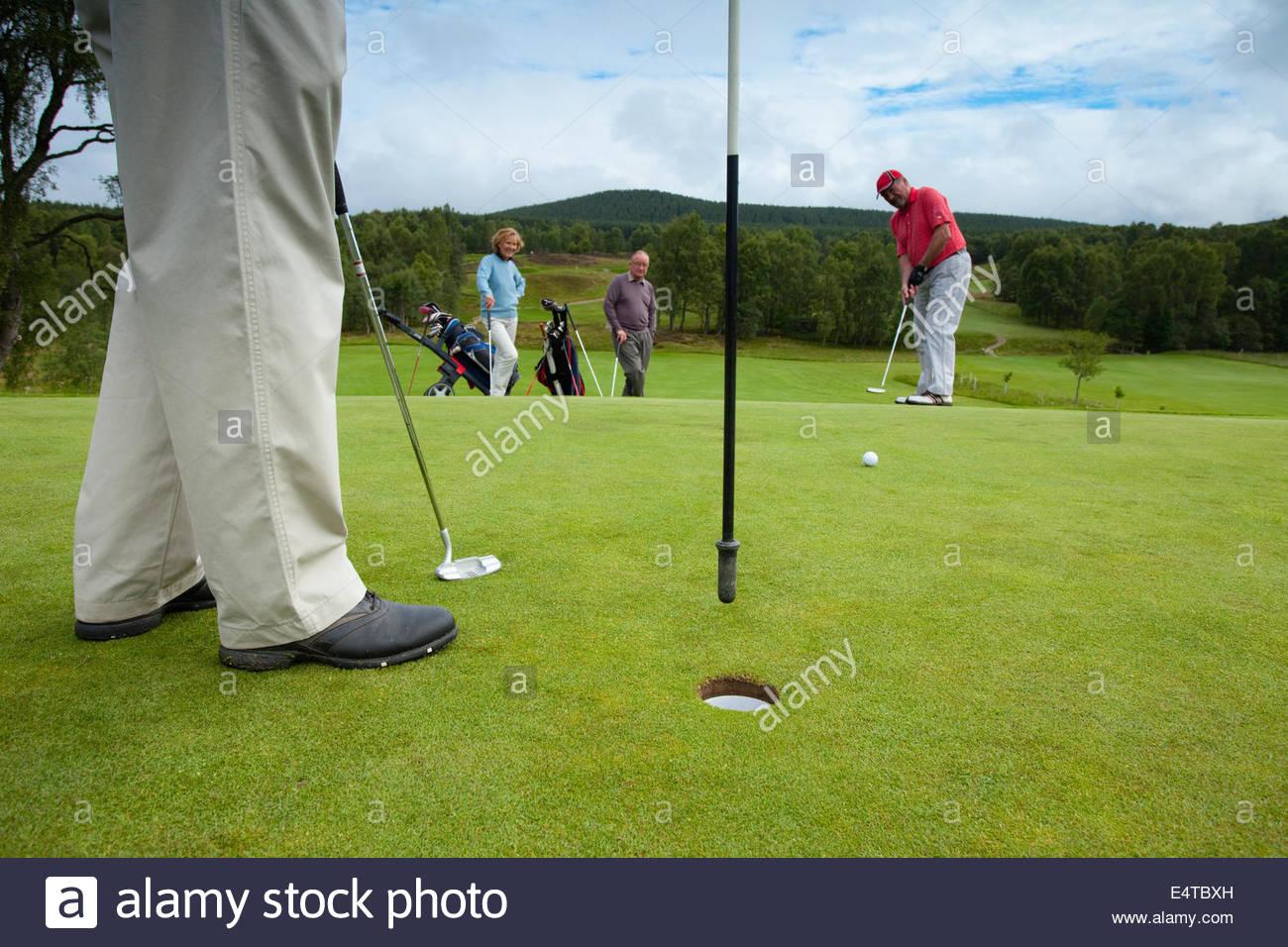 Cuatro personas jugar una ronda de golf en el Club de Golf en Carrbridge, Parque Nacional de Cairngorms, Highlands Imagen De Stock