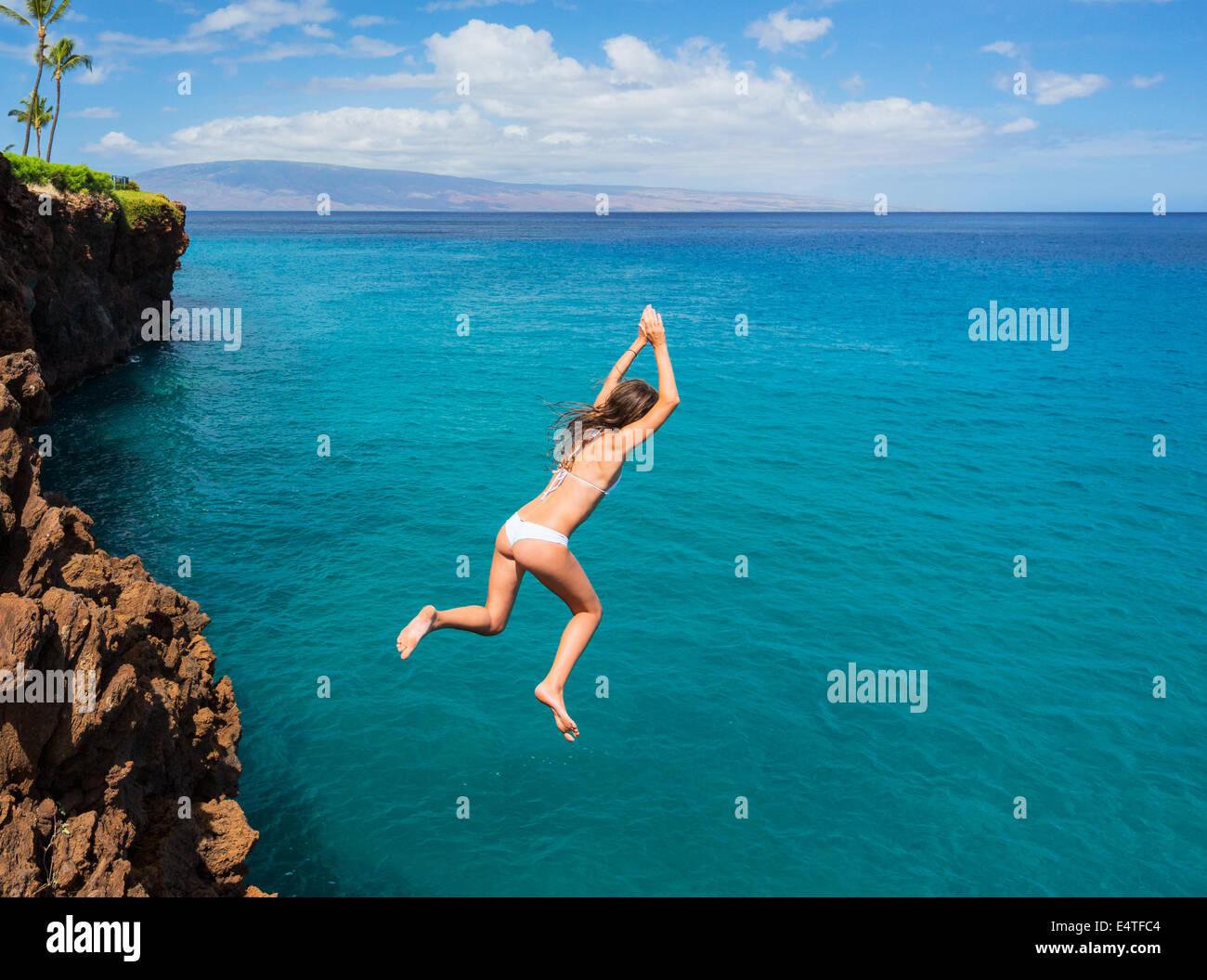 Mujer saltando desde el acantilado hacia el océano. Verano divertido estilo de vida. Imagen De Stock