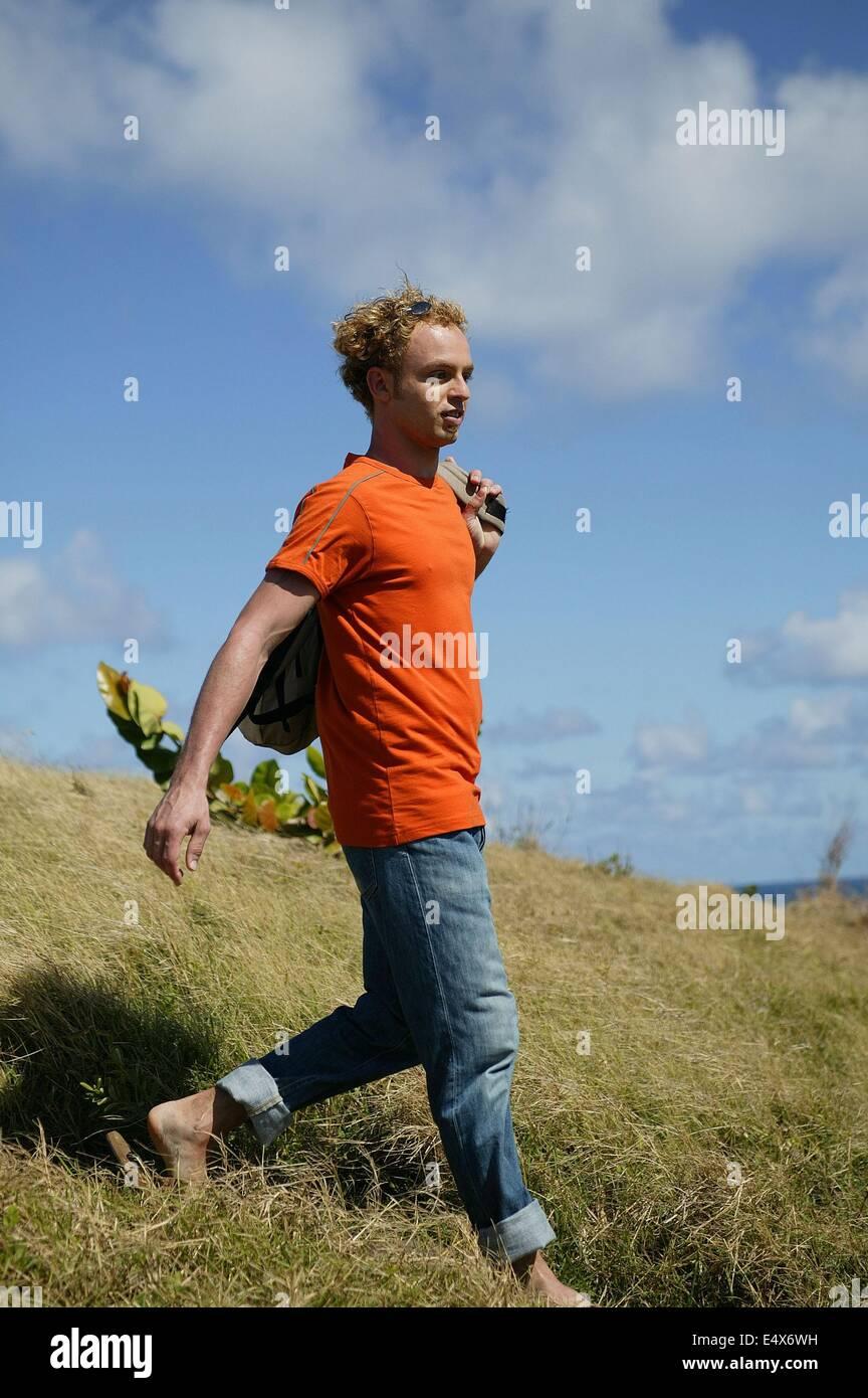 Hombre caminando por el campo con una mochila Foto de stock